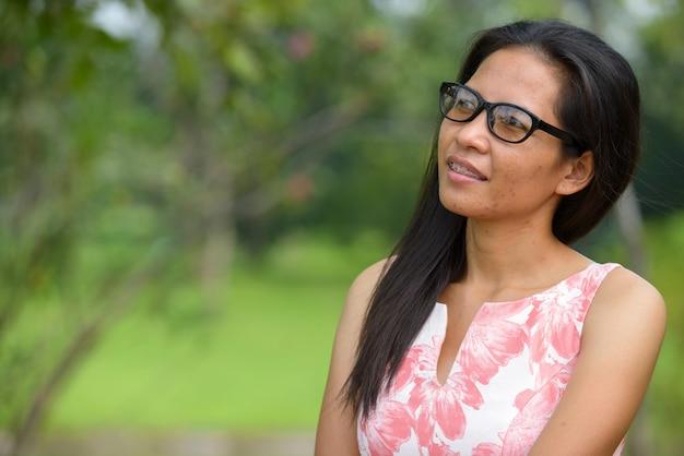 Portret van volwassen aziatische vrouw ontspannen in het park buiten