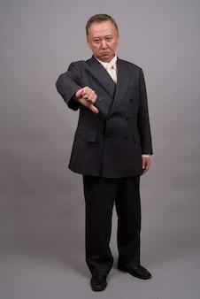 Portret van volwassen aziatische zakenman tegen grijze achtergrond