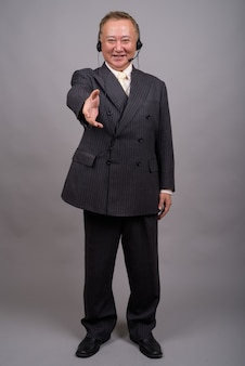 Portret van volwassen aziatische zakenman tegen grijze muur
