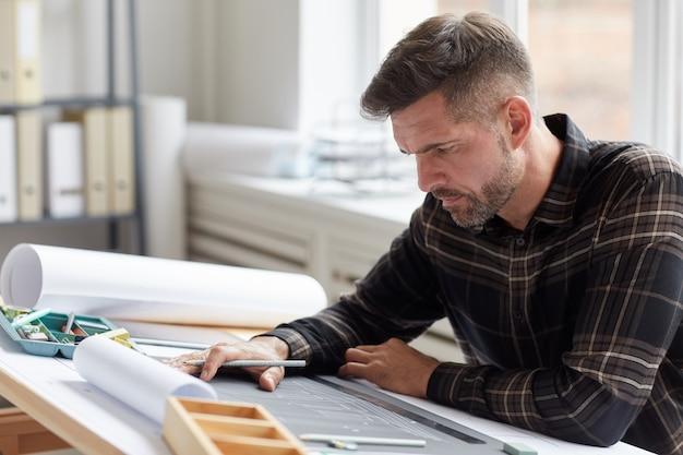 Portret van volwassen bebaarde architect bezig met blauwdrukken en plannen zittend op de tekentafel in kantoor,