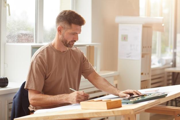 Portret van volwassen bebaarde architect blauwdrukken kijken zittend op de tekentafel in zonlicht,