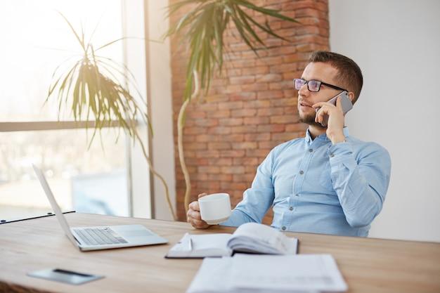 Portret van volwassen bebaarde drukke mannelijke bedrijfsdirecteur in glazen en blauw shirt zitten in lichte kantoor praten over de telefoon
