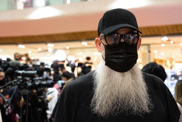 Portret van volwassen bebaarde hipster man met masker voor bescherming tegen coronavirus uitbraak sociale afstand nemen in het winkelcentrum