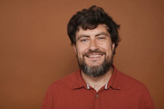 Portret van volwassen bebaarde man die lacht poseren op bruin