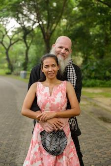 Portret van volwassen bebaarde man en volwassen aziatische vrouw als getrouwd stel