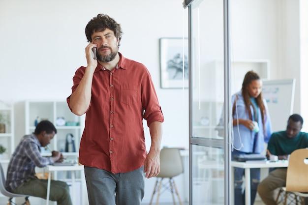 Portret van volwassen bebaarde man gekleed in vrijetijdskleding spreken door smartphone tijdens het wandelen in kantoor