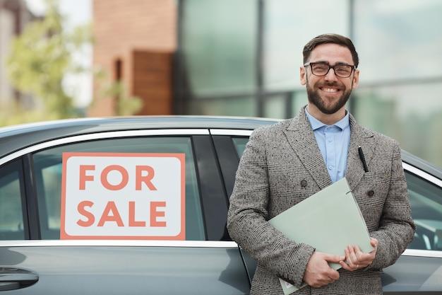 Portret van volwassen bebaarde man met documenten en glimlachen. hij koopt de auto