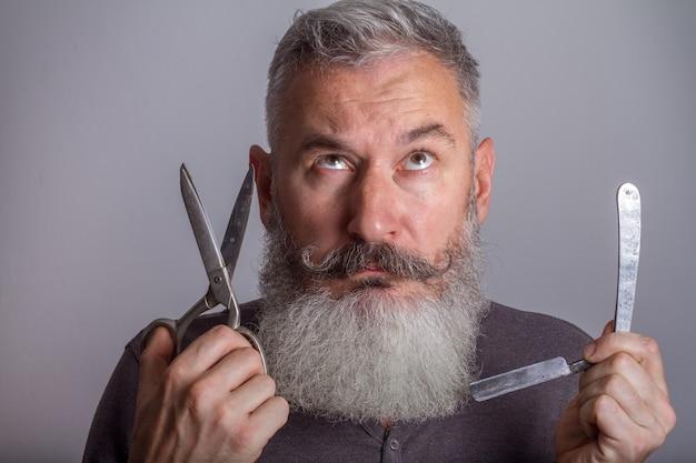 Portret van volwassen bebaarde man met retro scheermes en schaar