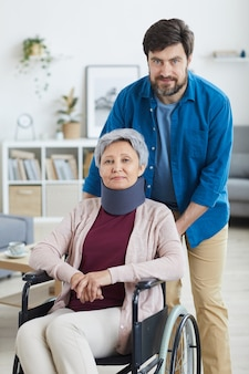 Portret van volwassen bebaarde man zorg over gehandicapte senior vrouw in rolstoel thuis