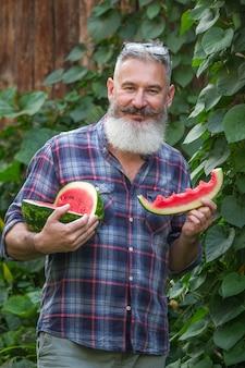 Portret van volwassen bebaarde mannelijke boer met rode rijpe watermeloen
