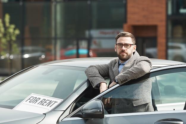 Portret van volwassen bebaarde zakenman in brillen terwijl hij in de buurt van de auto buiten staat