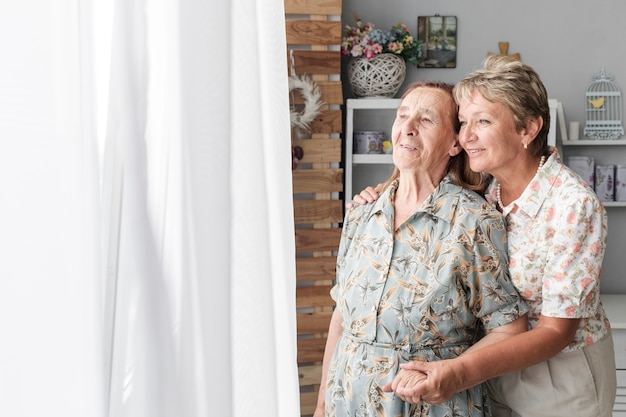 Portret van volwassen dochter met haar senior moeder thuis