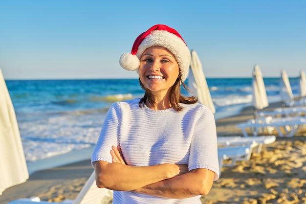 Portret van volwassen gelukkige vrouw in kerstmuts op het strand zee resort