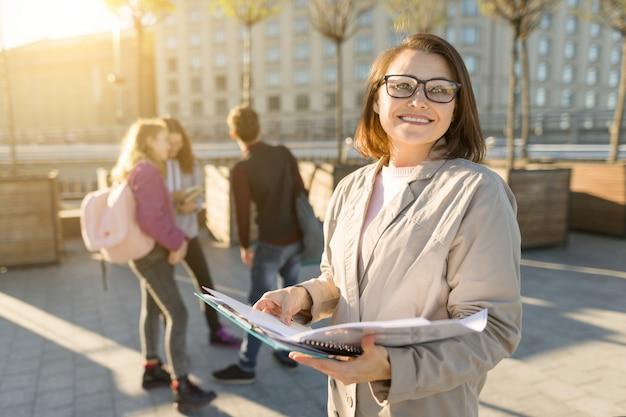 Portret van volwassen glimlachende vrouwelijke leraar in glazen
