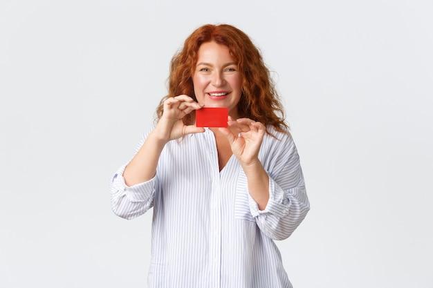 Portret van volwassen jaren '40 roodharige vrouw die creditcard met tevreden glimlach toont.