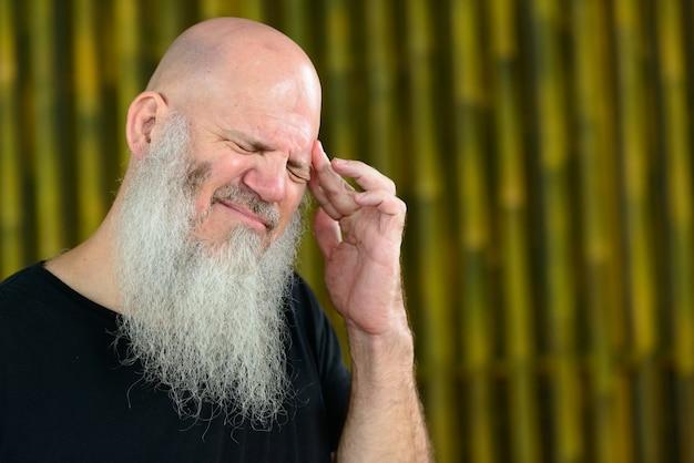 Portret van volwassen kale hipster man met lange baard tegen bamboe muur buitenshuis
