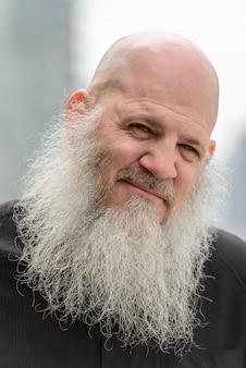 Portret van volwassen kale hipster man met lange baard tegen uitzicht over de stad buitenshuis
