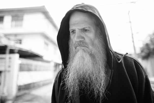 Portret van volwassen kale man met lange grijze baard in de straten buiten in zwart-wit