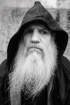 Portret van volwassen kale man met lange grijze baard tegen grunge betonnen muur buiten in zwart-wit
