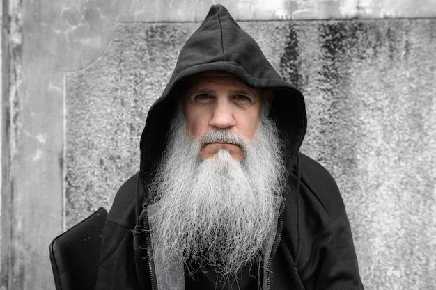 Portret van volwassen kale man met lange grijze baard tegen grunge betonnen muur buitenshuis