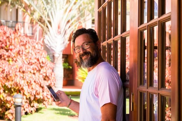 Portret van volwassen knappe bebaarde man die aan de telefoon belt en webapplicatie gebruikt op mobiel in het tuinpark buiten huis glimlachend naar de camera