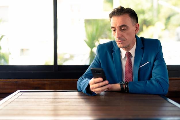 Portret van volwassen knappe italiaanse zakenman ontspannen in de koffieshop