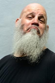 Portret van volwassen knappe kale hipster man met lange baard tegen betonnen muur