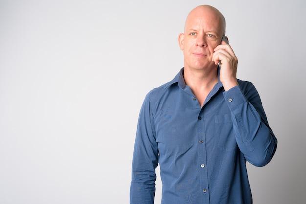 Portret van volwassen knappe kale zakenman praten aan de telefoon