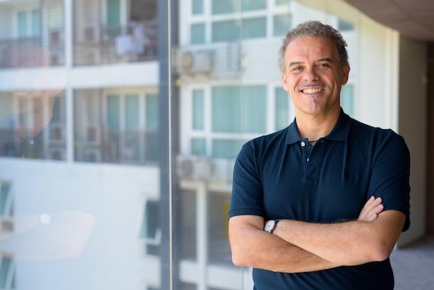 Portret van volwassen knappe man door het glazen raam van moderne, eigentijdse woning binnenshuis