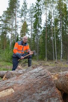 Portret van volwassen knappe man intensivering op stapel gehakt hout terwijl bijl in het bos