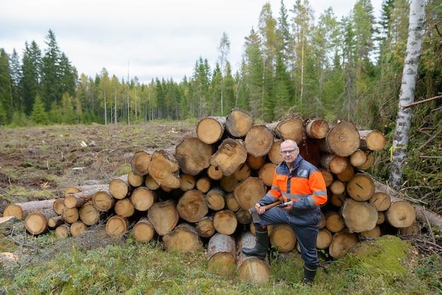 Portret van volwassen knappe man met telefoon en bijl gehakt hout buiten bos