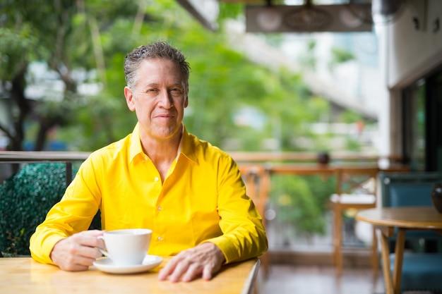Portret van volwassen knappe man zit in coffeeshop