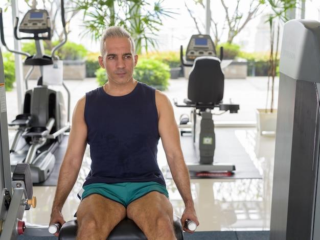 Portret van volwassen knappe perzische man met grijs haar die traint in de sportschool
