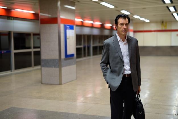 Portret van volwassen knappe zakenman in treinstation