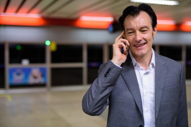 Portret van volwassen knappe zakenman praten over de telefoon in het treinstation