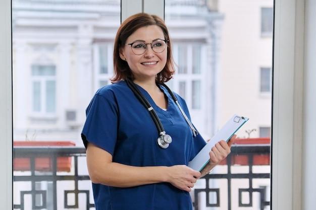 Portret van volwassen lachende arts met een stethoscoop klembord