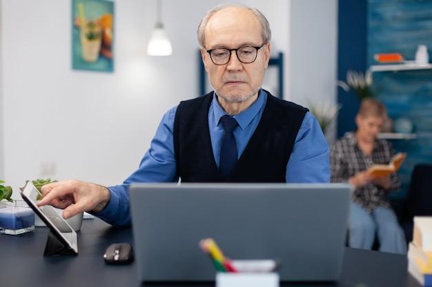 Portret van volwassen man die websurft op laptop vanuit kantoor aan huis