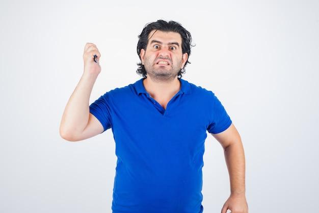 Portret van volwassen man dreigt met een schaar, tanden op elkaar klemmen in blauw t-shirt en op zoek agressief vooraanzicht