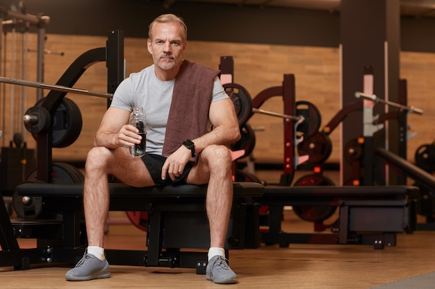 Portret van volwassen man drinkwater en camera kijken tijdens het zitten en rusten na sporttraining