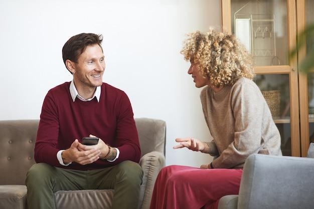 Portret van volwassen man en vrouw chatten zittend op de bank tijdens indoor party met vrienden