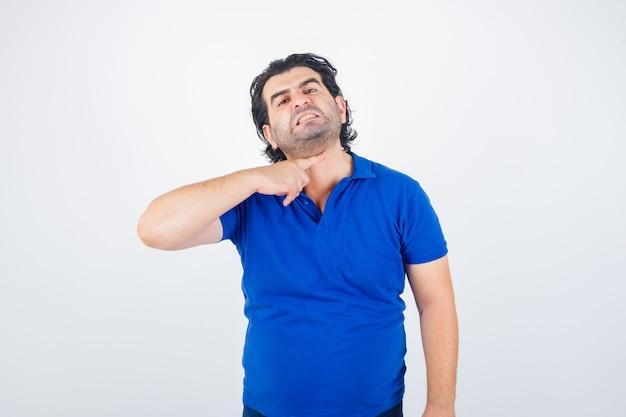 Portret van volwassen man gebaren met wijsvinger naar zijn nek alsof hij keel in blauw t-shirt doorsnijdt en agressief vooraanzicht kijkt