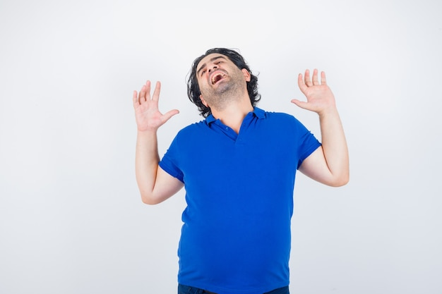 Portret van volwassen man geeuwen en rekken bovenlichaam in blauw t-shirt en op zoek slaperig vooraanzicht