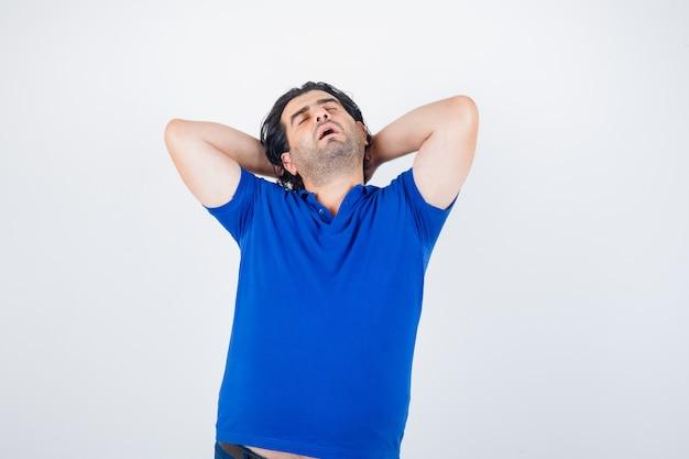 Portret van volwassen man hand in hand achter hoofd in blauw t-shirt en op zoek naar slaperig vooraanzicht
