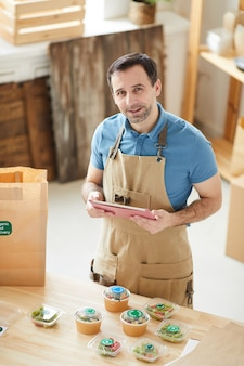 Portret van volwassen man met schort tijdens het verpakken van bestellingen aan houten tafel in de bezorgservice voor eten