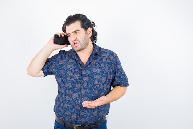 Portret van volwassen man praten op mobiele telefoon in shirt en boos vooraanzicht kijken