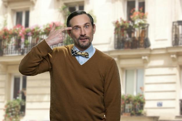 Portret van volwassen man toont headshot gebaar. dood me alsjeblieft. groot huis op de achtergrond.