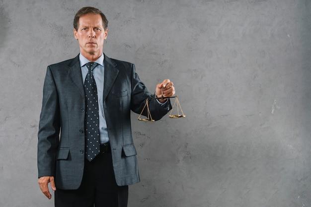 Portret van volwassen mannelijke advocaat houden rechtvaardigheid schaal tegen grijze gestructureerde achtergrond