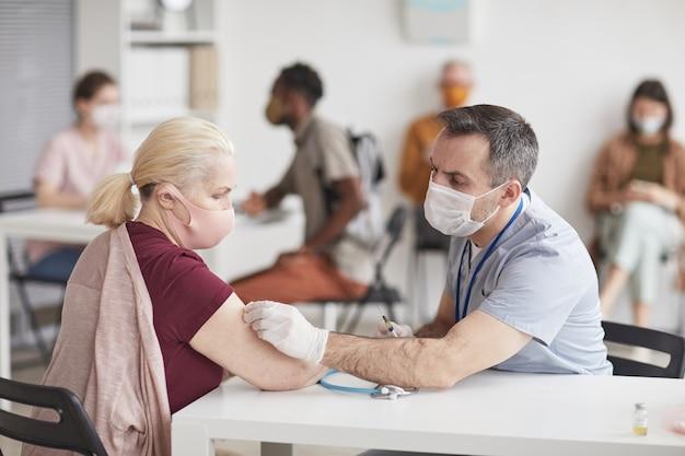 Portret van volwassen mannelijke arts die senior patiënt vaccineert in vaccinatiecentrum of kliniek, beide met maskers, kopieer ruimte