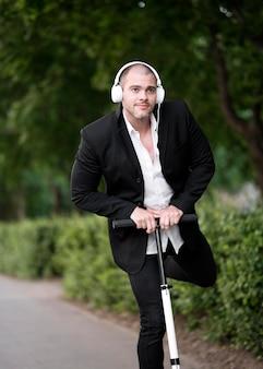 Portret van volwassen mannelijke rijden scooter met koptelefoon