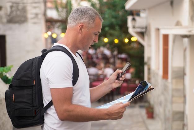 Portret van volwassen mannelijke wandelaar met behulp van slimme telefoon buitenshuis.